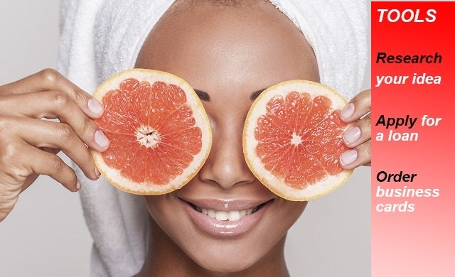 Natural spa. Beautiful young Afro-American shirtless woman holding pieces of orange in front of her eyes while standing isolated on gray background