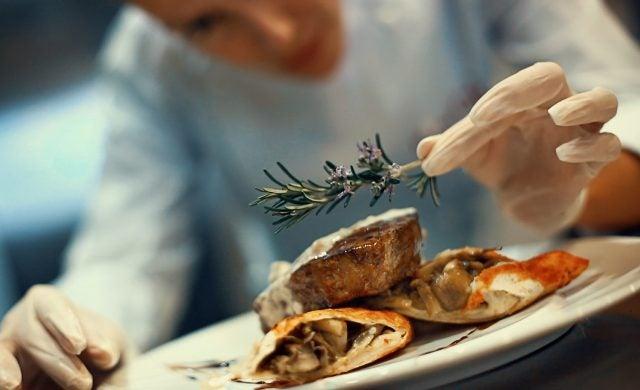 Chef prepares dish in kitchen