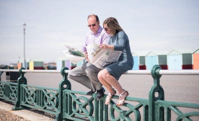 Jon Card and Corinne Card, founders of Full Story Media, sitting on railings