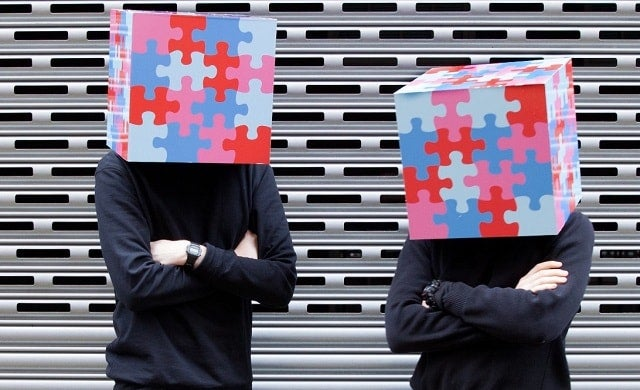 Founders of Jigtalk with their faces covered by jigsaw pieces