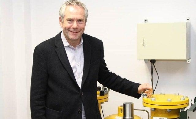 Adam Kingdon standing beside a gas system