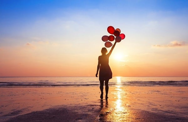 A woman on a beach holding balloons